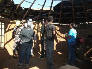 Guys plastering mud on inside of Tholakele's house