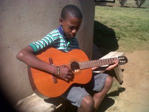 Menzi with Guitar given by someone at Coming King Ministries